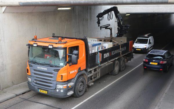 Vrachtwagen raakt spoorbrug met kraan